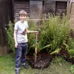 A boy in Bristol plants one of the 12,000 fruit trees that we're giving to children to plant in their home gardens.